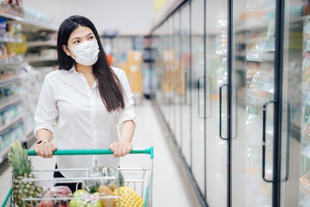 Asiatische frau, die mit maske einkauft, die sicher für lebensmittel, sicherheitsmaßnahmen im supermarkt kauft.