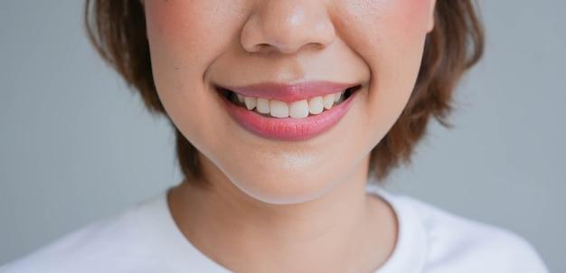 Asiatische frau, die mit schönem zahn für die zahngesundheit lächelt