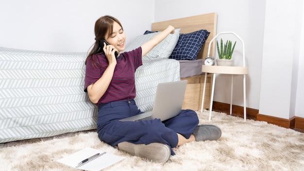 Asiatische frau, die mit smartphone oder tablet auf bett zu hause arbeitet