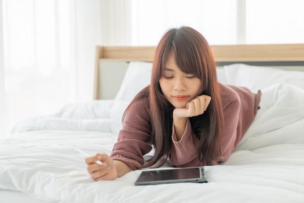 Asiatische frau, die mit tablette auf bett arbeitet