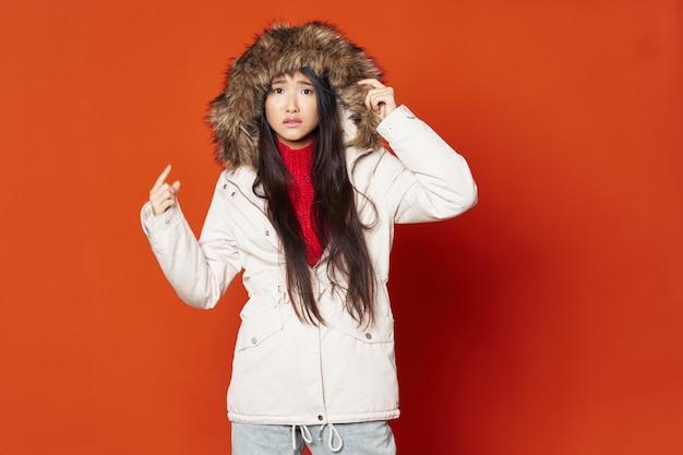 Asiatische frau, die mit winterkleidung aufwirft