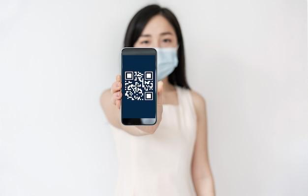 Asiatische frau, die mobiles smartphone mit qr-code-scan- und verifikationstechnologie auf dem bildschirm zeigt und chirurgische gesichtsmaske trägt