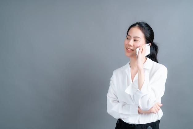 Asiatische frau, die mobiltelefon sprechendes geschäft lokalisiert auf grauer wand verwendet