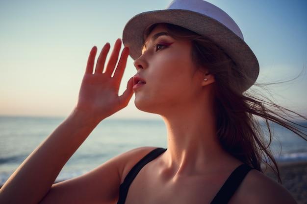 Asiatische frau, die modestrohstrandhut für hautpflege-sonnenschutz trägt