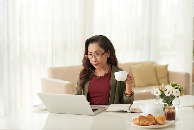 Asiatische frau, die morgens etwas auf laptop aufpasst
