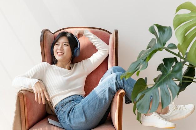 Asiatische frau, die musik auf einem roten sofa hört
