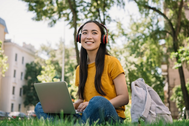 Asiatische frau, die musik hört und auf gras sitzt. student studieren, fernunterricht