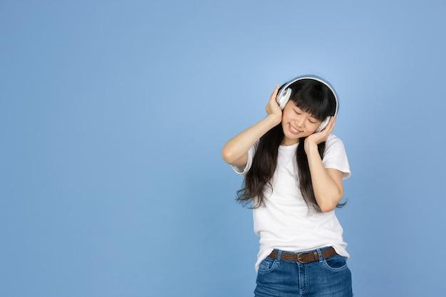 Asiatische frau, die musik mit kopfhörern auf blau hört