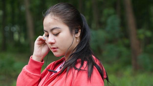 Asiatische frau, die musik nach dem laufen im wald hört