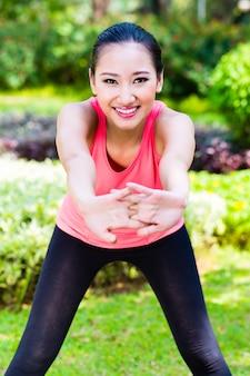 Asiatische frau, die muskeln für fitness im stadtpark streckt