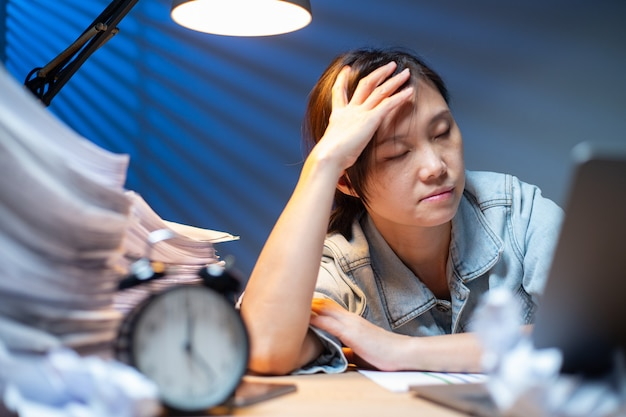Asiatische frau, die nachts dokumente in überstunden schreibt. arbeitsfrist im büro. offiziersmädchenkopfschmerzen und beschäftigt mit ihrem job.