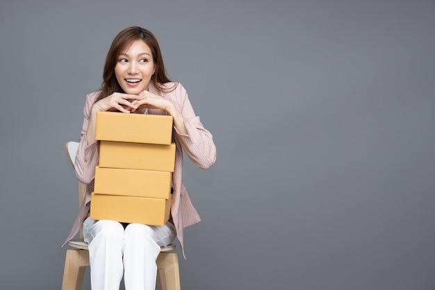 Asiatische frau, die paketkasten hält und auf weißem stuhl sitzt, isoliert auf grauem hintergrund