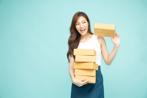 Asiatische frau, die paketpaketkasten lokalisiert auf grünem hintergrund hält