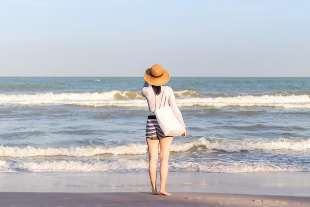 Asiatische frau, die panamhat und sonnenbrille, glückliches mädchen trägt, das entlang des strandes in der sommerzeit geht