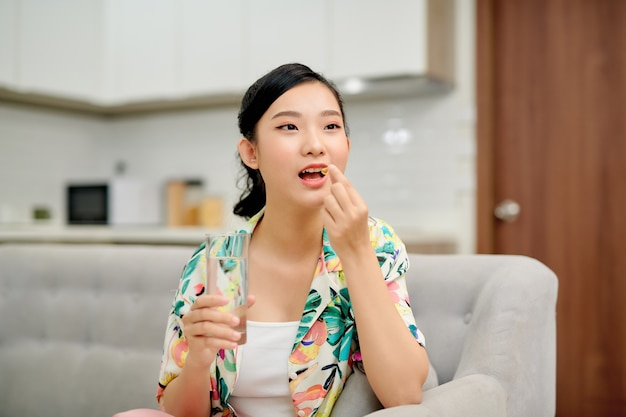 Asiatische frau, die pille und ein glas wasser hält, das auf sofa sitzt.