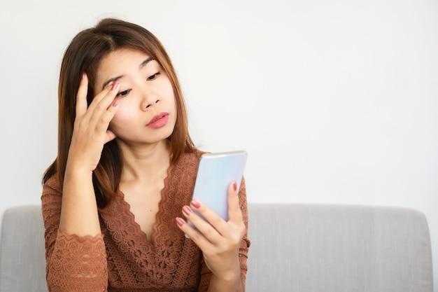 Asiatische frau, die problem mit augenschmerzen hat, die vom betrachten des handybildschirms müde sind