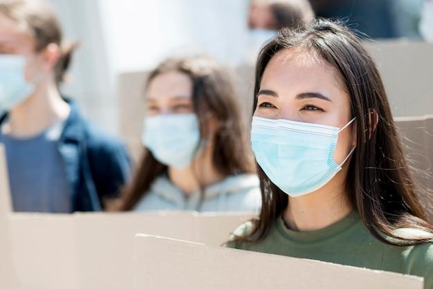 Asiatische frau, die protestiert und medizinische maske trägt