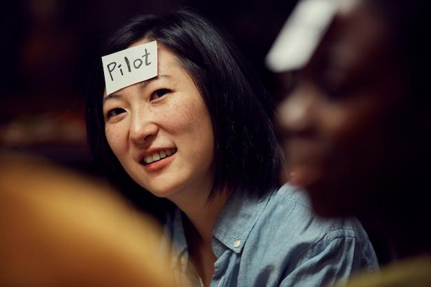 Asiatische frau, die ratespiel spielt
