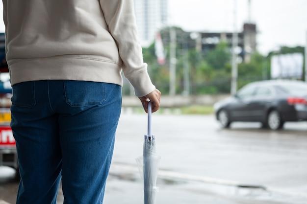 Asiatische frau, die regenschirm hält, während taxi wartet und auf der bürgersteigstraße der stadt im regnerischen tag steht.