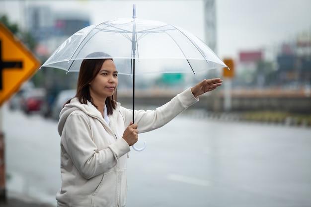Asiatische frau, die regenschirmtrampen-taxi an der stadtstraße am regnerischen tag hält.