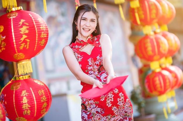 Asiatische frau, die rotes traditionelles chinesisches cheongsam trägt und rote umschläge in der hand hält