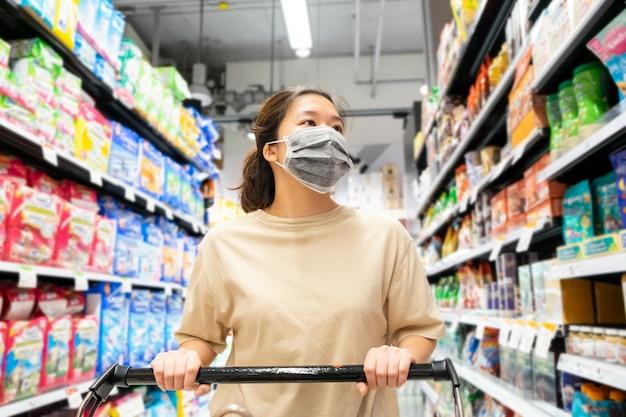 Asiatische frau, die schützende gesichtsmaske mit einkaufswagen am supermarkt trägt
