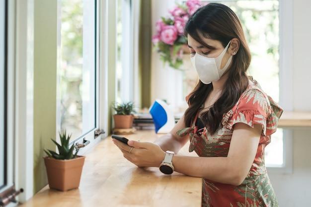 Asiatische frau, die schützende gesichtsmaske trägt und smartphone im restaurant verwendet, schützt coronavirus-beugung. soziale distanzierung, neue normalität und leben nach der covid-19-pandemie