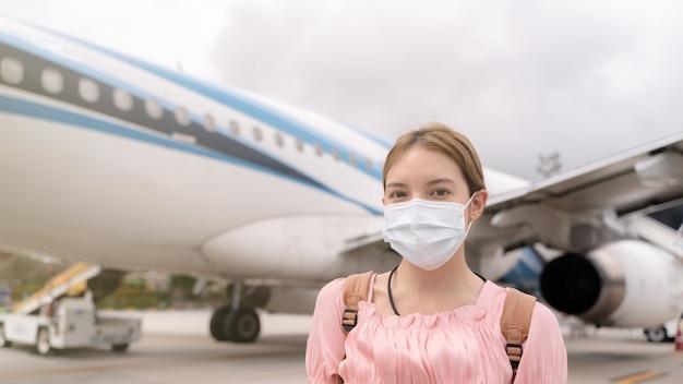 Asiatische frau, die schützende gesichtsmaske während der covid-19-viruspandemie trägt, geht zur treppe, die flugzeug betritt, parken außerhalb des terminals im flughafen.