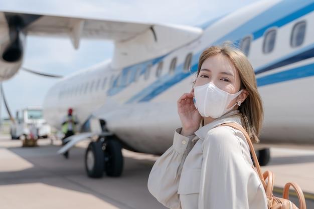 Asiatische frau, die schützende gesichtsmaske während der covid19 viruspandemie trägt