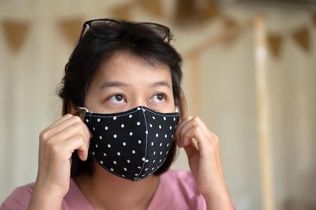 Asiatische frau, die schutzmaske auf ihrem gesicht trägt