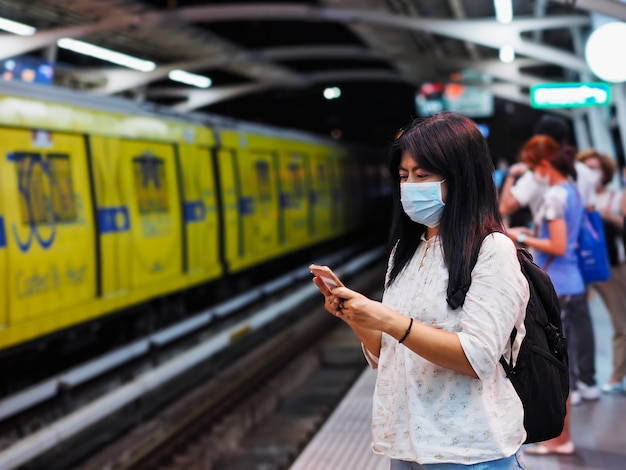 Asiatische frau, die schutzmaske trägt und handy während des wartenden skytrains spielt.