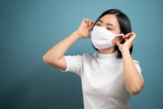 Asiatische frau, die schutzmaske zum schutz vor virus und krankheit auf blau isoliert trägt