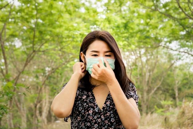 Asiatische frau, die schutzmasken trägt, die draußen gehen