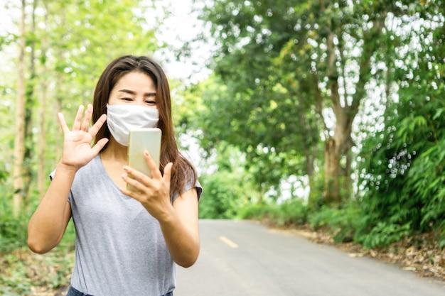 Asiatische frau, die schutzmaskenvideoanruf mit jemandem trägt