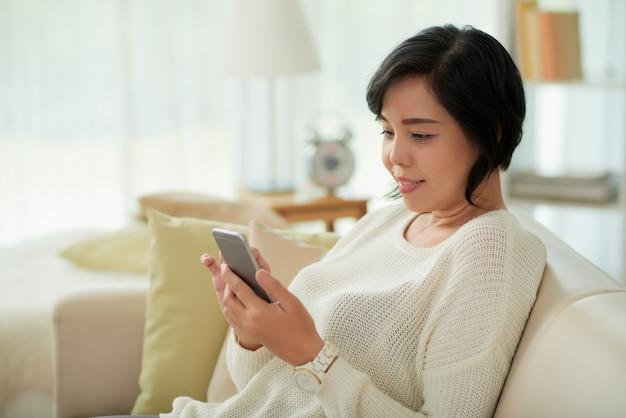 Asiatische frau, die sich zu hause unter verwendung des smartphone entspannt