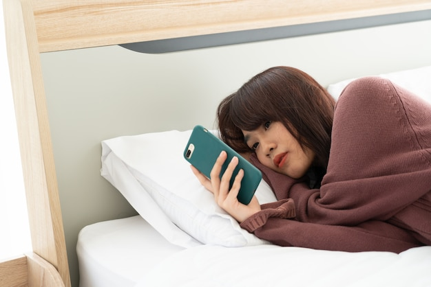 Asiatische frau, die smartphone auf bett spielt