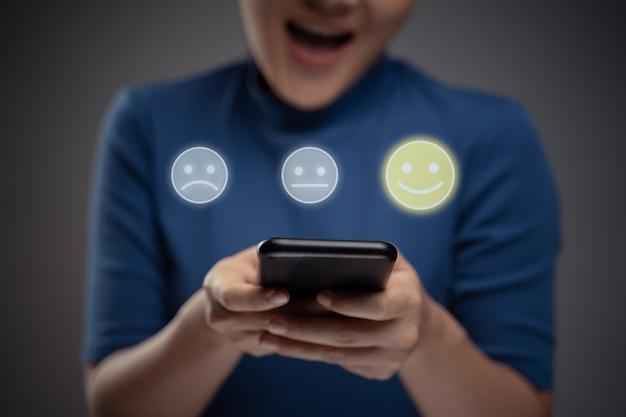 Asiatische frau, die smartphone für die abstimmung mit emoticon-hologramm-effekt verwendet. isoliert