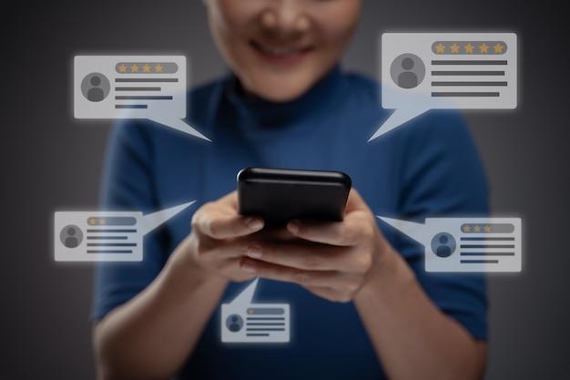 Asiatische frau, die smartphone für rückmeldung, bewertungen mit kommentaren symbol hologramm-effekt verwendet. isoliert