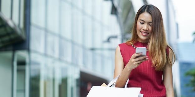 Asiatische frau, die smartphone mit einkaufstaschen hält
