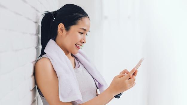 Asiatische frau, die smartphone nach dem spielen yoga und übung zu hause verwendet