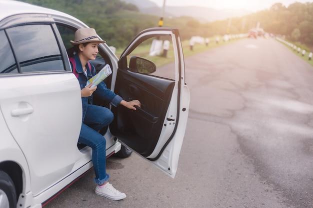 Asiatische frau, die smartphone und karte zwischen fahrendem auto auf straßenfahrt verwendet