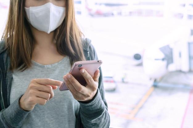 Asiatische frau, die smartphone verwendet und chirurgische maske am flughafenterminal trägt. gesundheitskonzept