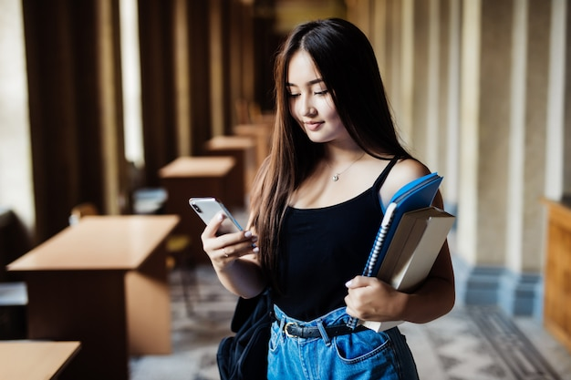 Asiatische frau, die sms auf handy in universitätscampus sendet