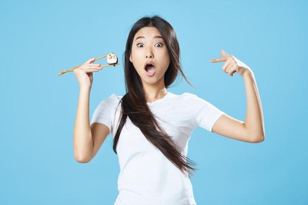 Asiatische frau, die sushi-rollen mit stäbchen hält