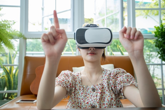 Asiatische frau, die tablet und virtual-reality-simulator verwendet, die spiele im wohnzimmer spielen und sich glücklich fühlen. lebensstil seniorenfamilie zu hause konzept