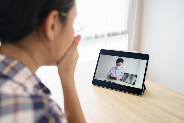 Asiatische frau, die tablette verwendet, um untersuchungsergebnisse von ärzten auf einer fernbedienung zu konsultieren