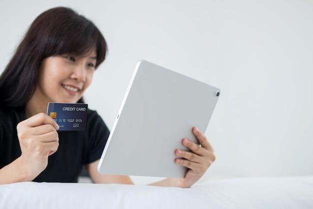 Asiatische frau, die tablette verwendet