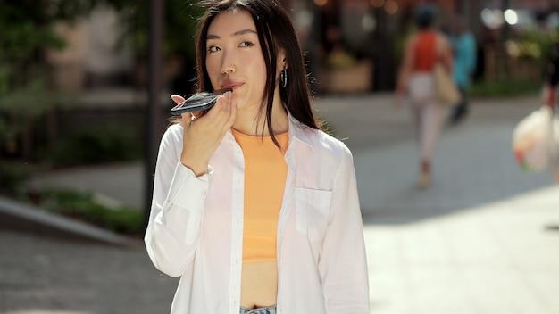 Asiatische frau, die telefon spricht, aktiviert virtuellen digitalen sprachassistenten auf smartphone-mädchen mit smartphone-spracherkennung diktiert gedanken-sprachanwahlnachricht