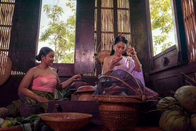Asiatische frau, die thailändisches kleid kostüm traditionell gemäß kultur und tradition kocht in der küche am alten haus ayutthaya, thailand trägt
