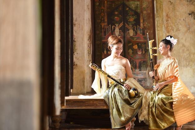 Asiatische frau, die traditionelle thailändische kultur, weinlesestil, thailand-kultur trägt